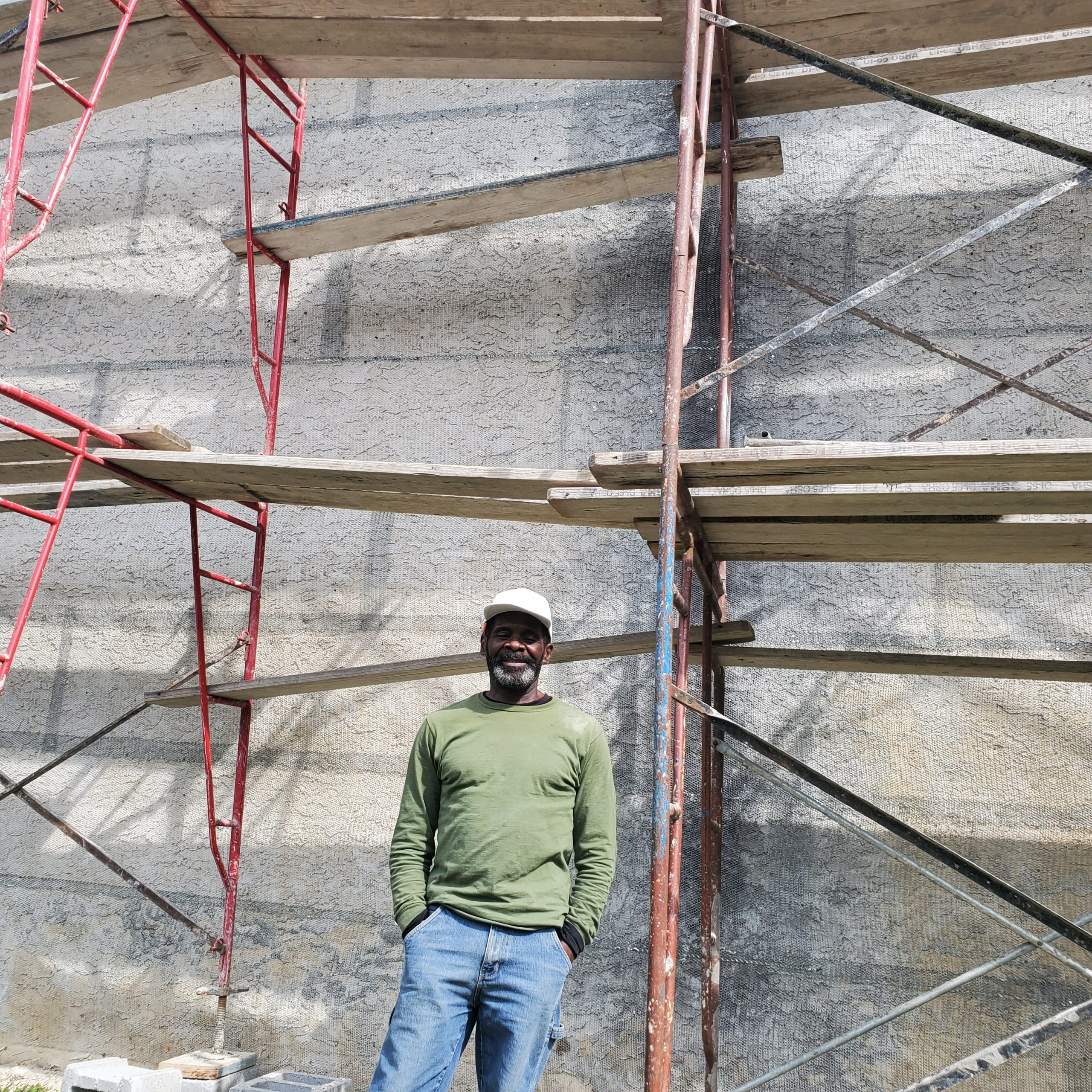Rudy the Stucco Guy in front of the mural wall with a scaffold behind him.