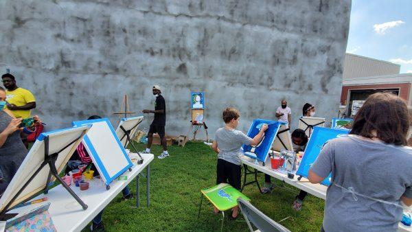 Paint class outside on grass.