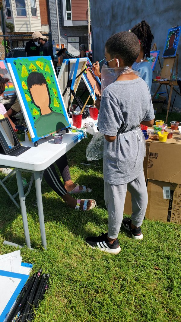 Youth male standing in front of his canvas portrait.