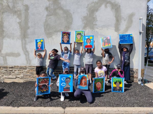 Selfie Project youth holding up their painted self portaits.